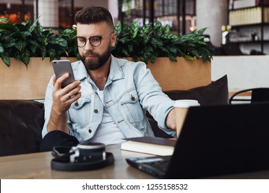 Bearded hipster man in trendy glasses sits in cafe at table, works on laptop, uses smartphone. On table is notebook and camera. Freelancer works remotely. Online marketing, adult education,training.