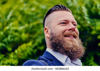 Bearded hipster over green bush background.