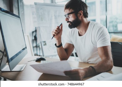 Bearded hipster professional wearing eye glasses working at modern loft studio-office with desktop computer.White blank display screen.Blurred background. Horizontal