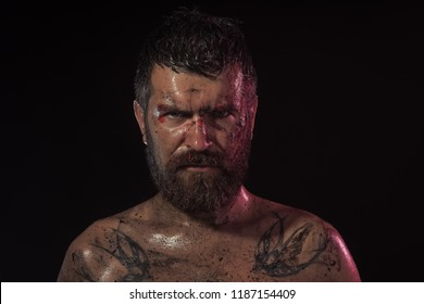 Bearded hipster with tattoo on chest on black background. Wizard, sorcerer, warlock. Man with beard, mustache on brutal bloody face. Magic, enchantment, witchcraft. Halloween, holidays celebration