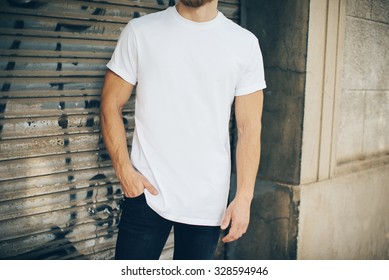 Bearded hipster wearing white blank t-shirt and blue jeans, standing on the street