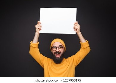 Bearded hipster in yellow hat and sweatshirt holding blank white poster above head on black background