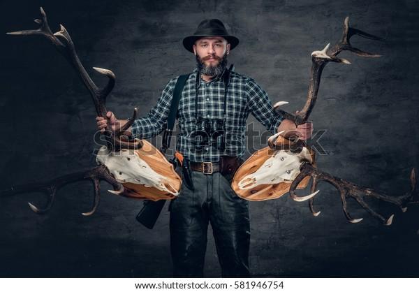 The bearded hunter male holds a two deer's skull.