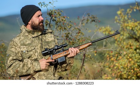 Bearded hunter spend leisure hunting. Hunting equipment for professionals. Hunting is brutal masculine hobby. Man aiming target nature background. Hunter hold rifle. Aiming skills. Hunting permit.