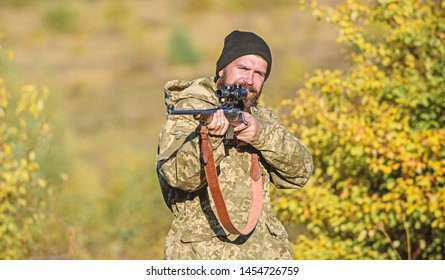Bearded hunter spend leisure hunting. Focus and concentration of experienced hunter. Hunting masculine hobby concept. Man brutal gamekeeper nature background. Regulation of hunting. Hunter hold rifle.