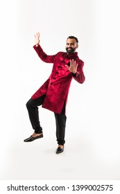 Bearded Indian Man performing desi dance steps while wearing traditional kurta/sherwani, celebrating wedding or party, isolated over white background