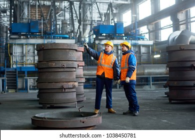 Bearded inspector wearing reflective vest and hardhat pointing at something while young technician giving tour of modern factory, interior of spacious production department on background