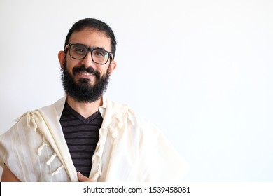 Bearded Jewish with a  Tallit (talis) and Praying. The man is standing in front of a white background