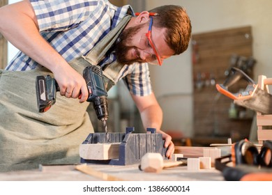Bearded joiner in safety glasses drills an electric drill hole in a wooden Board in a home workshop repairing wooden products