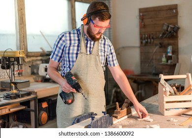 Bearded joiner in safety glasses drills electric drill hole in a wooden Board in the home workshop in the basement