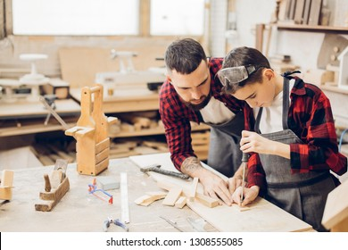 Bearded jointer adult man watching as his young little son in safety glasses and an apron works with chisel in a carpentry shop.