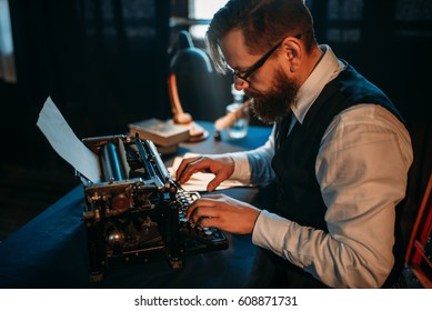 Bearded journalist in glasses typing on typewriter