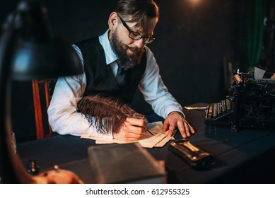 Bearded journalistr in glasses writes with feather