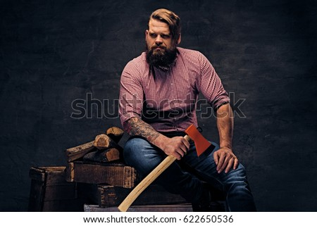 5249e45b A bearded lumberjack with tattoo on arms, dressed in a pink fleece shirt  holds the
