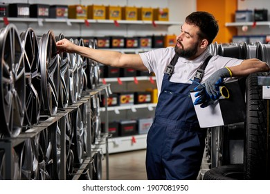 bearded male auto mechanic repairman examining car rims, checking the assortment in his shop, at work place, wearing uniform