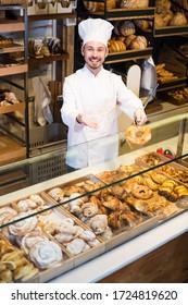 Bearded male baker showing assortment of bakery