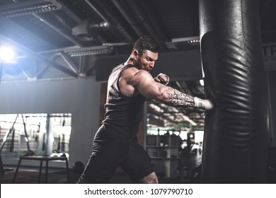 Bearded Male boxer training with punching bag in dark sports hall. Young tattoed boxer training on punching bag. Male boxer as exercise for the big fight. Cool tone.