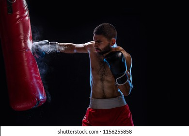 Bearded male boxer training with punching bag on black background. Male boxer as exercise for the big fight.