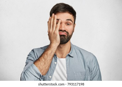 Bearded male brunet covers face as shows his tiredness, curves lips, has no desire to work, dressed in denim shirt, isolated over white concrete background. Frustrated man with indignant look
