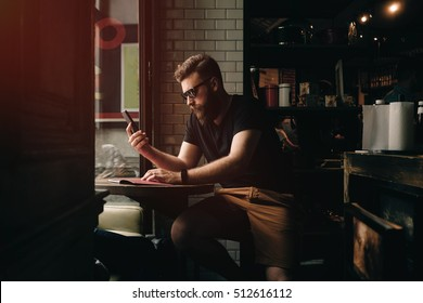 A bearded male is checking e-mail on a smartphone while waiting for the cup of tea in a cute city coffee shop with loft interior. Hipster guy in sunglasses is surfing the web on a mobile phone.