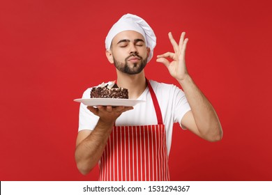 Bearded male chef cook or baker man in striped apron toque chefs hat posing isolated on red background. Cooking food concept. Mock up copy space. Hold plate with cake, making okay taste delight sign