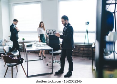 Bearded male colleague in black business suit using mobile phone standing next to table near coworkers moving to workplace in office