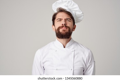 Bearded male cook with a cap on his head on a gray background