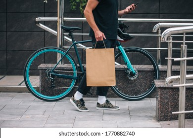 Bearded male courier with bicycle delivery food service at home. Shopping paper bag with copy space for your text or advertising content. No name shopping bag