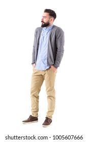 Bearded male fashion model in gray cardigan with hands in pockets looking away. Full body length portrait isolated on white studio background.