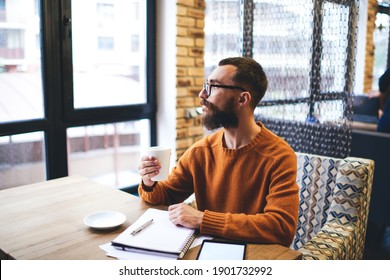 Bearded male freelancer pensively looking out window and drinking tea while working remotely with notepad and tablet in cozy restaurant
