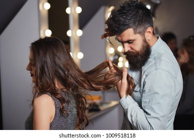 Bearded male hairdresser cutting clients hair with scissors at hair salon. Hairdresser cutting hair, does a hairstyle of girl client. Beautiful woman getting haircut by hairdresser at barber shop.