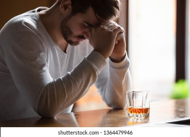 Bearded male hold head with hands look down sitting on bar counter feels depressed desperate, drinking strong alcoholic drink, having serious dependence alcoholism, alcohol use disorder (AUD) concept