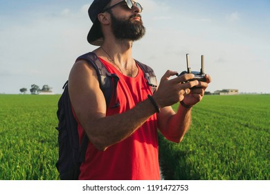 Bearded male model use drone remote control to fly device in air. Man operating drone flying in nature. New technologies and innovations concept. Sunlight effects