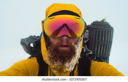 bearded male mountaineer takes a selfie in a winter whiteout conditions, reflection of arms in the goggles