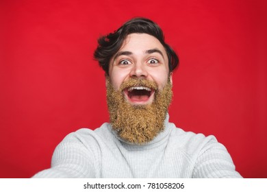 Bearded male person making a selfie pic over red background. Man with winter shiny glitter in beard