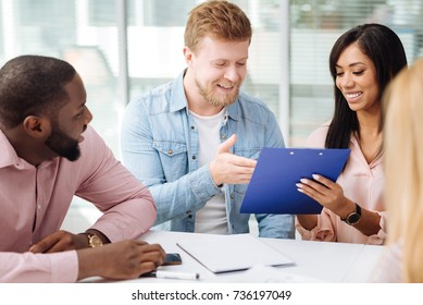 Bearded male person pointing at folder with document