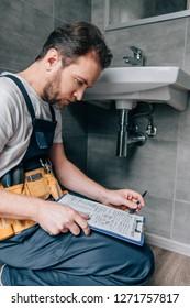 bearded male plumber with toolbelt writing in clipboard near broken sink in bathroom