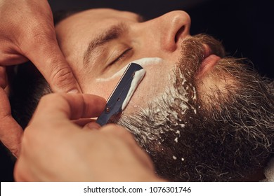 Bearded male sitting in an armchair in a barber shop while hairdresser shaves his beard with a dangerous razor.