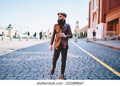 Bearded male tourist in fashionable apparel walking across Red Square with takeaway caffeine beverage during holidays in Russia, stylish man looking away while strolling on old city streets