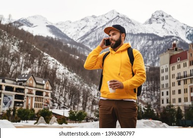 Bearded male tourist in yellow hoodie and cap with black backpack stands on background of high snowy mountains, talking on mobile phone, drinking coffee. Traveler walks, calling friends. Lifestyle