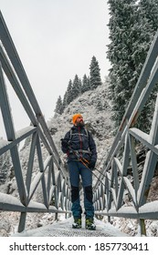 Bearded male traveler walks outdoors in winter. A guy stands on a bridge over a mountain river. Forest in the mountains after a snowfall