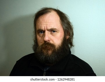 Bearded man 50 years old with blue eyes.Wrinkles on the forehead of a man. Serious, angry man close-up. A man similar to Dostoevsky.