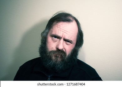 Bearded man 50 years old with blue eyes.Wrinkles on the forehead of a man. Bewilderment, disgust, skepticism. Skeptic.