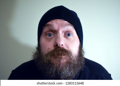 Bearded man 50 years old in black clothes and a hat. Bearded man with wide open blue eyes. Comic pose scarer, villain. Mimicry scary person.