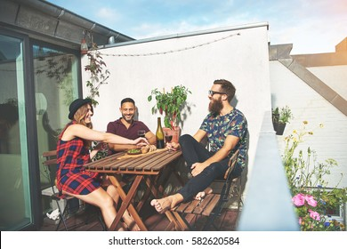 Bearded man with attractive young couple drinking wine at wooden table on roof in European city