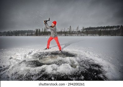 Bearded man with an ax chops ice at the lake