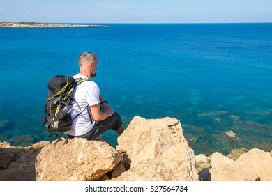 Bearded man with backpack sits on the rocky shore  and  looking at the sea. Sunny day on Cape Greco, Cyprus. Back view.