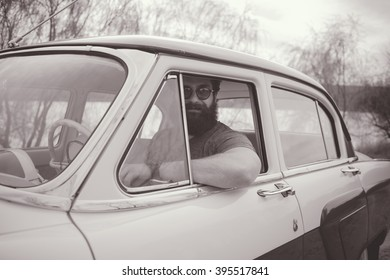 Bearded man behind the wheel of a retro car