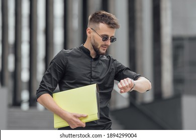 Bearded man in black dress in glasses looking at his watch