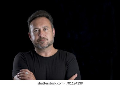Bearded man in a black shirt over black background with copy space